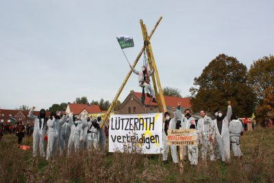 """Menschen in weißen Anzügen stehen um einen Tripod herum und halten ein Transpi mit """"Lützerath verteidigen"""""""